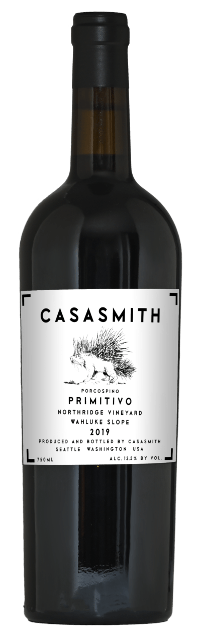 A tall dark Italian style bottle of wine. Black capsule on top and white label with black text that reads: CasaSmith Porcospino Primitivo, Wahluke Slope.
