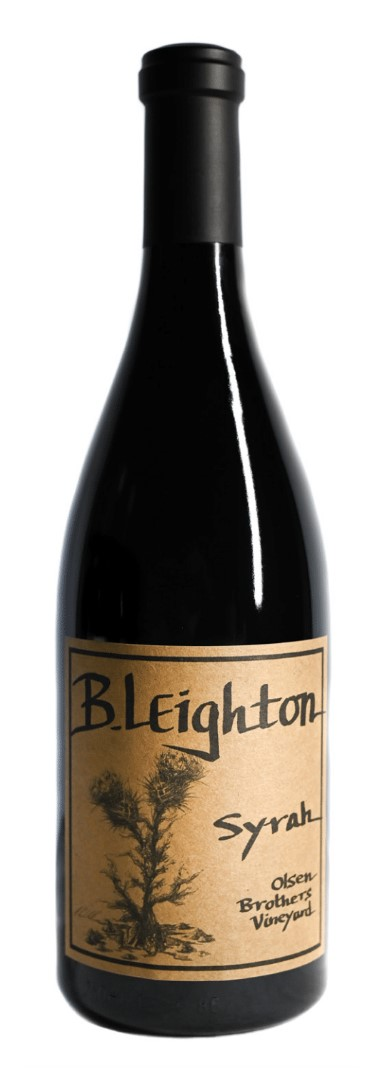 A classy dark bottle with dark wine inside. A black capsule on top and a brown label with black text.